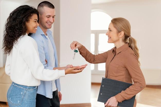 Agente de bienes raíces femenino entregando a pareja las llaves de su nuevo hogar Foto gratis