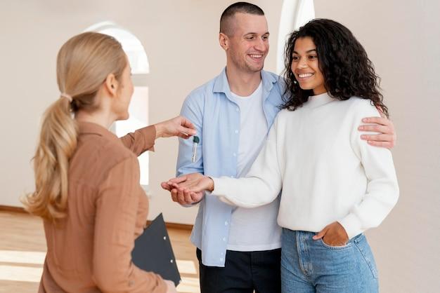 Agente de bienes raíces femenino entregando a la pareja sonriente las llaves de su nuevo hogar Foto gratis