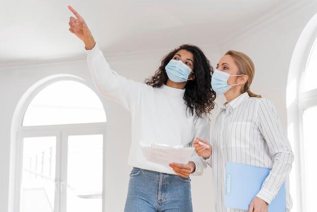Agente de bienes raíces femenino con máscara médica que muestra la casa a la mujer Foto gratis