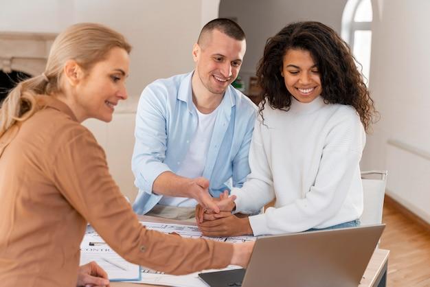 Agente de bienes raíces femenino que muestra la nueva casa a la pareja sonriente en la computadora portátil Foto gratis