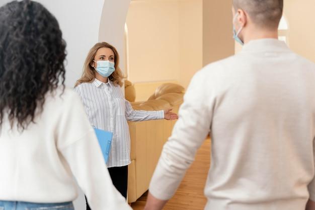 Agente de bienes raíces mujer con máscara médica invitando a la pareja a ver la nueva casa Foto gratis