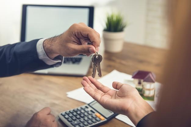 Agente de bienes raíces que entrega las llaves de la casa al cliente Foto Premium