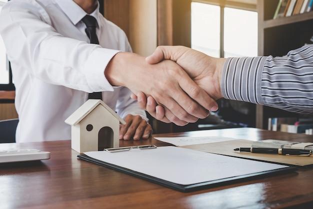 Agente de bolsa y cliente dándose la mano después de firmar los documentos del contrato Foto Premium