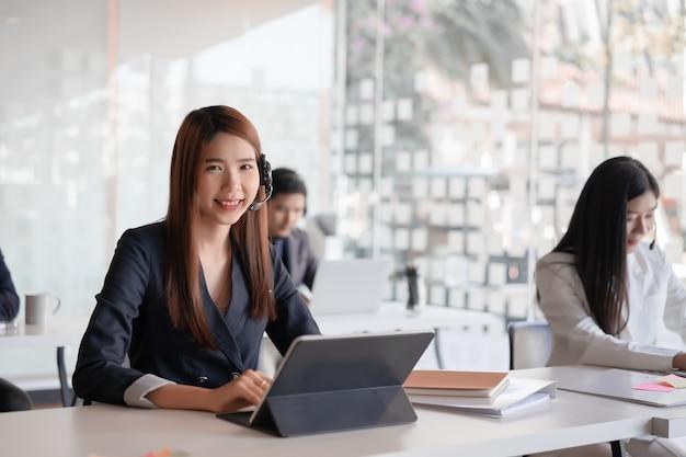 Agente femenino asiático hermoso del centro de atención telefónica en cliente de la consultoría de las auriculares. Foto Premium