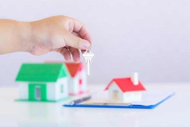 Agente inmobiliario con casa modelo y llaves. Foto gratis