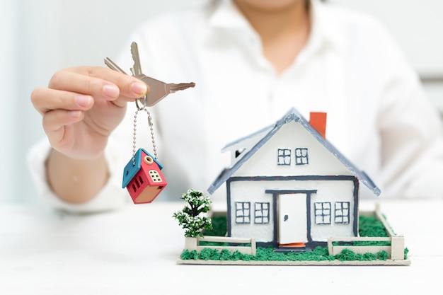 Agente inmobiliario con casa modelo y llaves Foto gratis