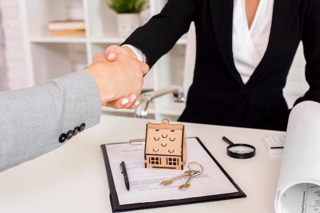 Agente inmobiliario estrechándole la mano al cliente Foto gratis
