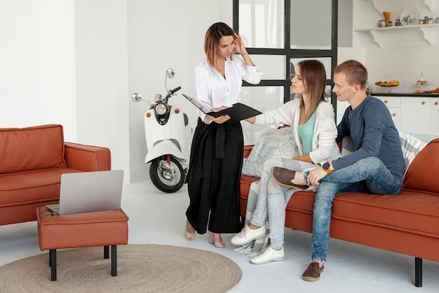 Agente inmobiliario hablando con hombre y mujer Foto gratis