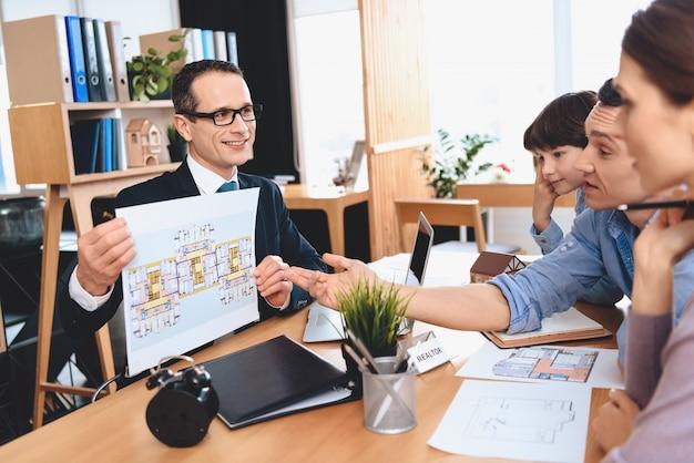 El agente inmobiliario está mostrando la disposición del apartamento a la familia. Foto Premium