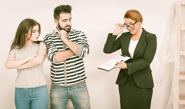Agente inmobiliario muestra acuerdo de escrúpulos a joven pareja en casa abierta Foto Premium