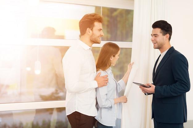 El agente inmobiliario le muestra la propiedad a una pareja joven. Foto Premium