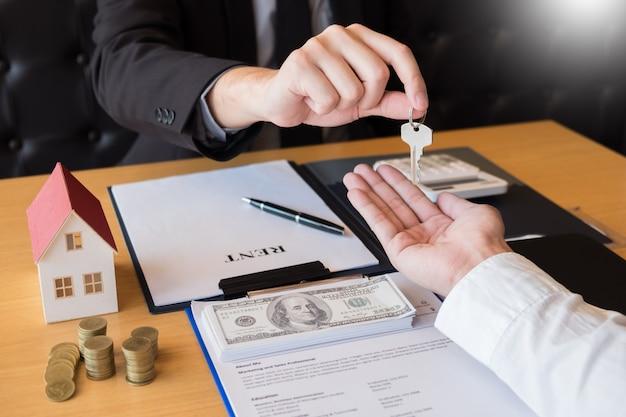 Agente inmobiliario que entrega la casa clave cliente firma acuerdo de propiedad Foto Premium