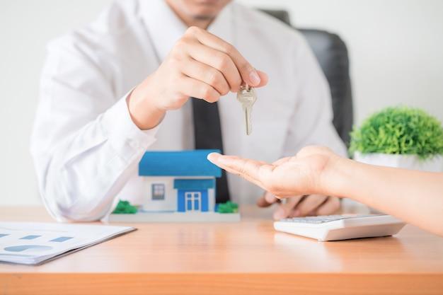 Agente inmobiliario que entrega una llave del departamento al nuevo propietario Foto gratis