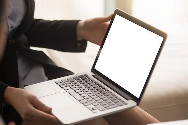 Agente inmobiliario de sexo femenino que muestra plan de la casa en la pantalla del ordenador portátil Foto gratis