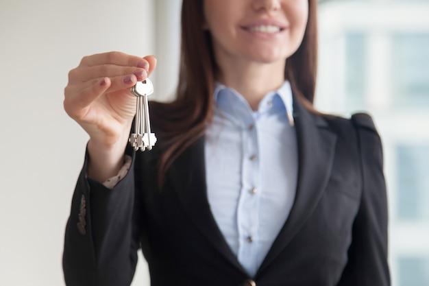 Agente inmobiliario de sexo femenino que sostiene llaves, concepto de compra de compra de propiedad Foto gratis