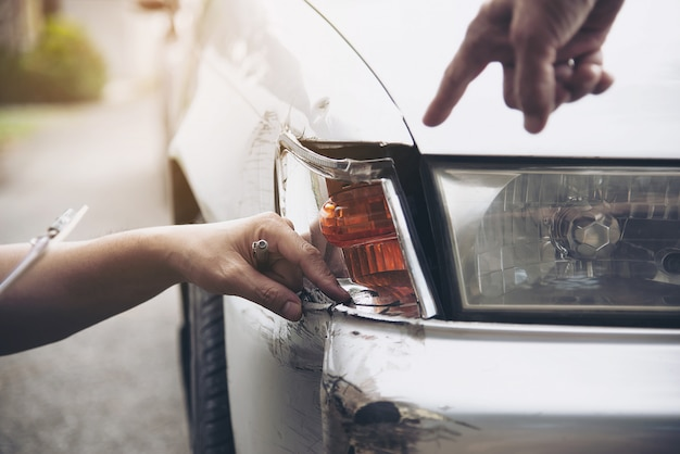 Agente de seguros que trabaja durante el proceso de reclamo de accidentes automovilísticos en el lugar, reclamo de seguro de personas y automóviles Foto gratis