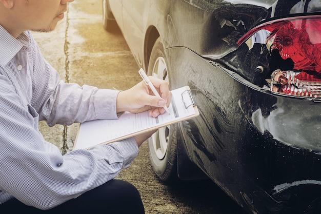 Agente de seguros trabajando en el proceso de reclamo de accidente de coche Foto gratis