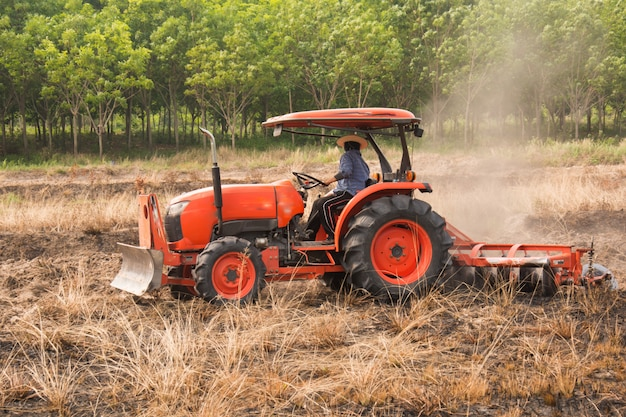Agricultor arando campo de rastrojo con tractor naranja Foto Premium
