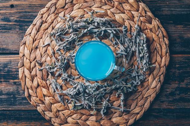 Agua de color azul en un salvamanteles con vista superior de té sobre un fondo oscuro de madera Foto gratis