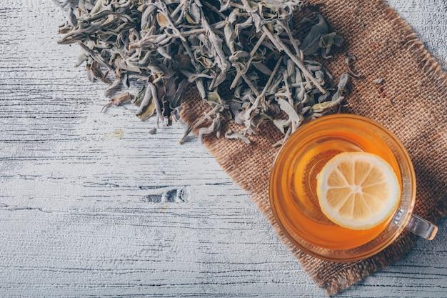 Agua de color naranja con vista superior de hierbas de té sobre una tela de saco y fondo de madera gris. espacio para texto Foto gratis