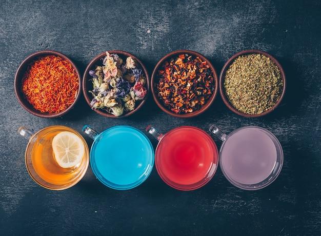 Agua coloreada en tazas con hierbas de té en tazones planos sobre un fondo oscuro con textura Foto gratis