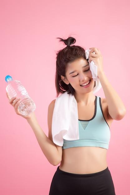 Agua potable hermosa joven apta del ajuste después del ejercicio Foto gratis