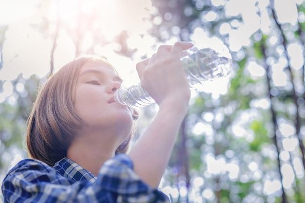 Agua potable de la muchacha hermosa de la botella plástica con salida del sol Foto Premium