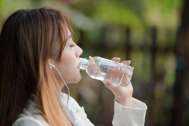 Agua potable de la mujer asiática de la botella por la mañana y música que escucha en fondo natural. Foto Premium