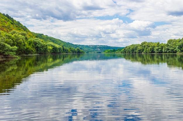 El agua del primer plano del río dniéster con bosques a los lados hechos de un barco. Foto Premium