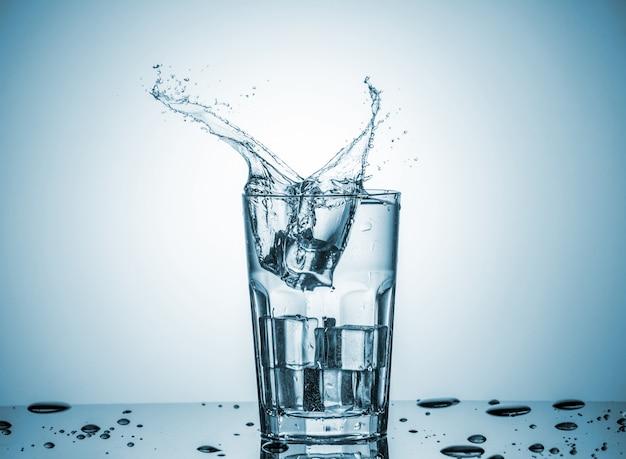 Agua en vaso con salpicaduras de agua Foto gratis