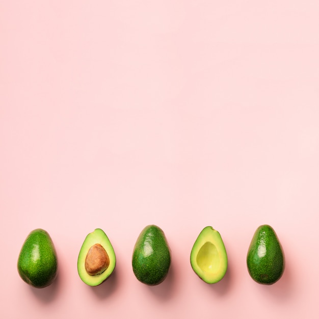 Aguacate orgánico con semilla, mitades de aguacate y frutas enteras sobre fondo rosado. patrón de aguacates verdes en estilo minimalista. Foto Premium