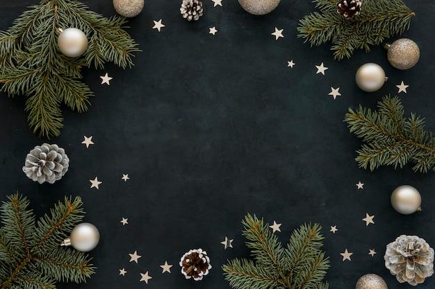 Agujas de pino natural y globos navideños sobre fondo oscuro Foto Premium