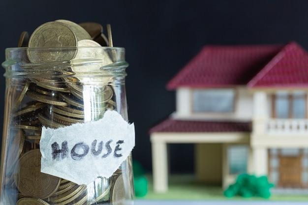 Ahorro de dinero para la casa en la botella de vidrio. Foto gratis