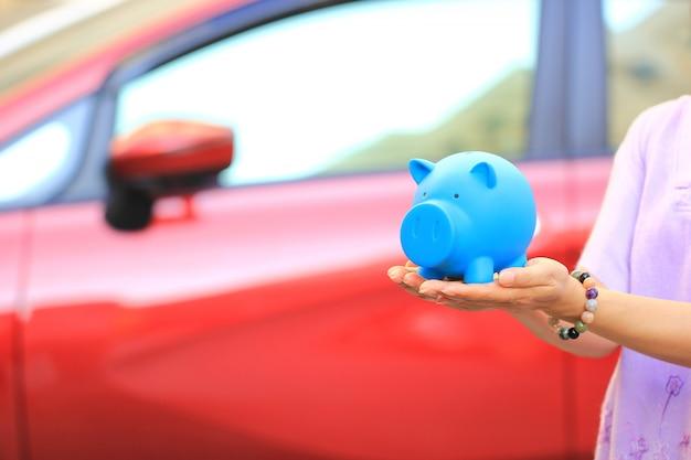 Ahorro de dinero y préstamos por concepto de automóvil, mujer joven con cerdito azul de pie en el aparcamiento, negocio de automóviles Foto Premium