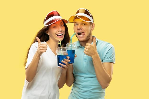 Aislado retrato de medio cuerpo de la hermosa joven pareja. mujer y hombre de pie con bebidas en gorras de colores. expresión facial, verano, concepto de fin de semana. colores de moda. Foto gratis