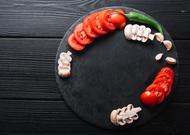 Ají verde; dientes de ajo con rodajas de setas y tomates en superficie de madera negra Foto gratis
