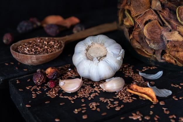 Ajo, frutos secos y semillas en una superficie rústica oscura. foto artística de ajo y fruta seca en la vieja mesa negra filmada en estilo discreto ciaroscurro Foto Premium