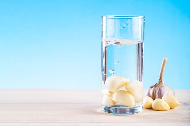 Ajo en un vaso de agua sobre agua azul, ajo, prevención de ...