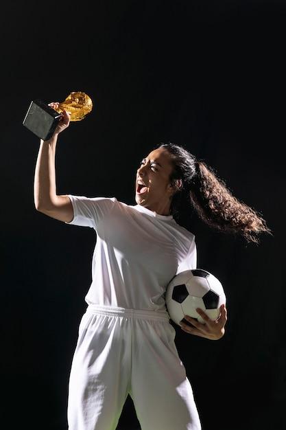 Ajuste fútbol mujer sosteniendo el trofeo Foto gratis