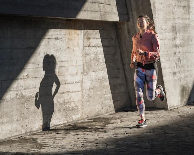 Ajuste hembra joven corriendo al aire libre Foto gratis