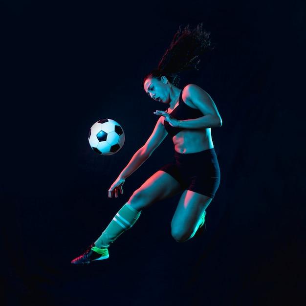 Ajuste joven pateando el balón de fútbol Foto gratis