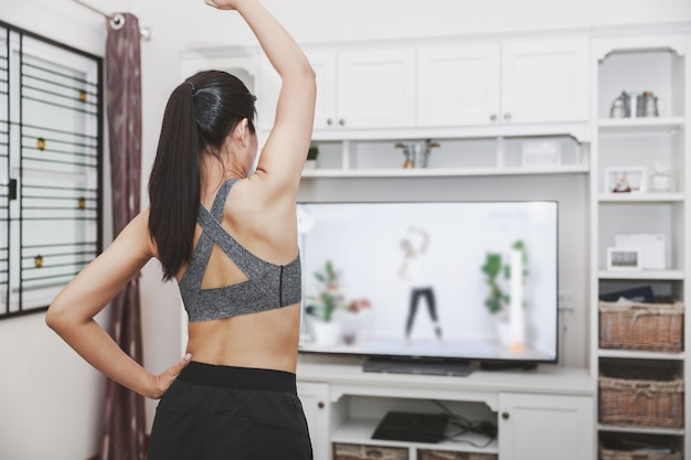 Ajuste mujer asiática entrenamiento fitness ejercicio deporte entrenamiento clase en línea en la televisión desde casa Foto Premium