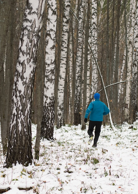 Al hombre le gusta correr en el bosque de invierno. Foto Premium