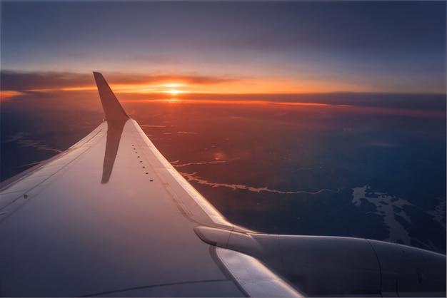 Ala del aeroplano durante una puesta del sol vibrante Foto Premium