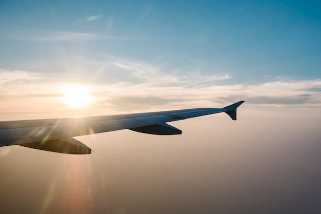 Ala de avión y puesta de sol en el cielo azul Foto gratis