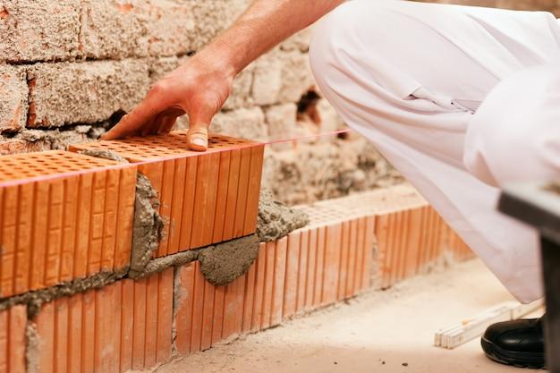 Albañil haciendo muro con ladrillo y lechada. Foto Premium