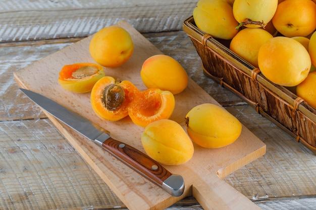 Albaricoques con cuchillo en una cesta en madera y tabla de cortar, vista superior. Foto gratis