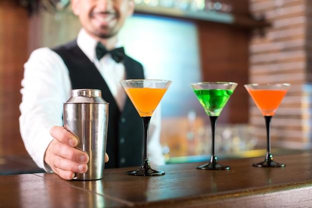Alegre barman muestra cómo hace cócteles. Foto Premium