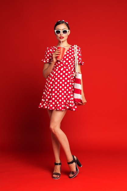 Alegre chica morena pin-up con refresco Foto Premium