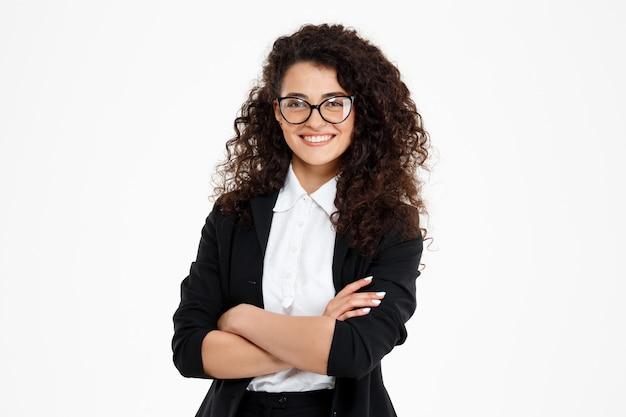 Alegre chica de negocios rizada con gafas Foto gratis